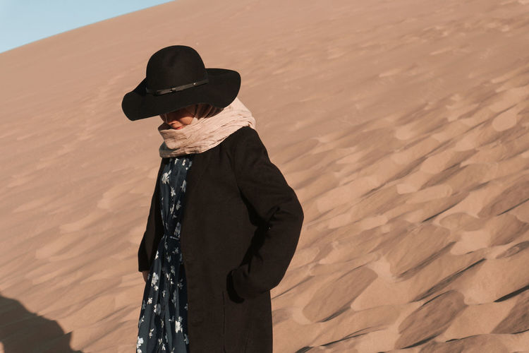 Man wearing hat standing on sand