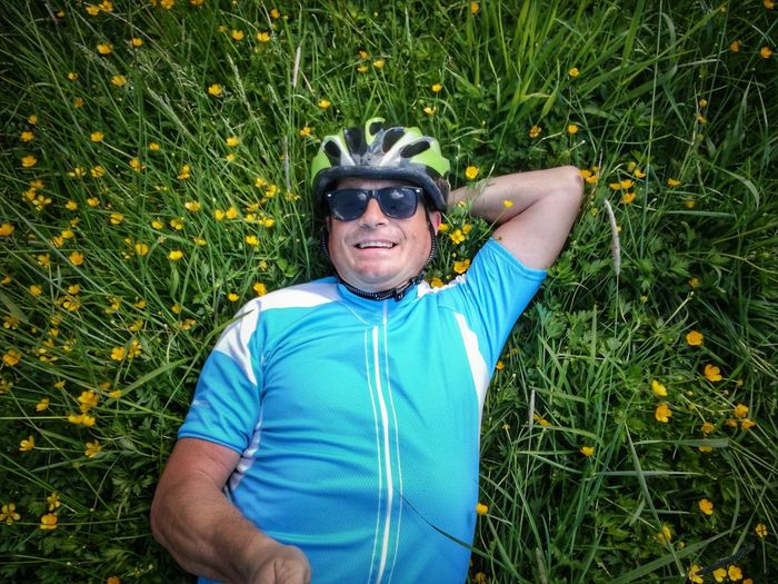 High Angle Portrait Of Smiling Mature Man Lying On Grassy Field