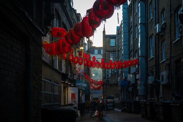 Low angle view of lanterns hanging amidst buildings in city