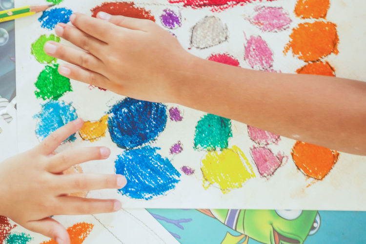Cropped image of hands over colorful sketch pad
