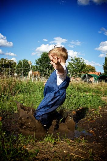 Boy Casual Clothing Childhood Children Cloud - Sky Coulds Countryside Day Elementary Age Full Length Grass Happy Joy Jumping Kids Mud Muddy Outdoors Playing Preschool Age Puddle Sky Splashing Toddler  Water