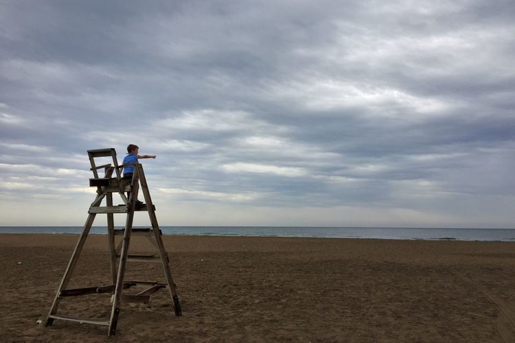 Boy standing on lifeguard chair at beach against cloudy sky