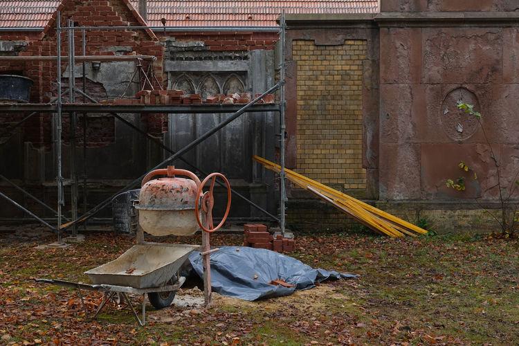 Abandoned wheelbarrow on land against building