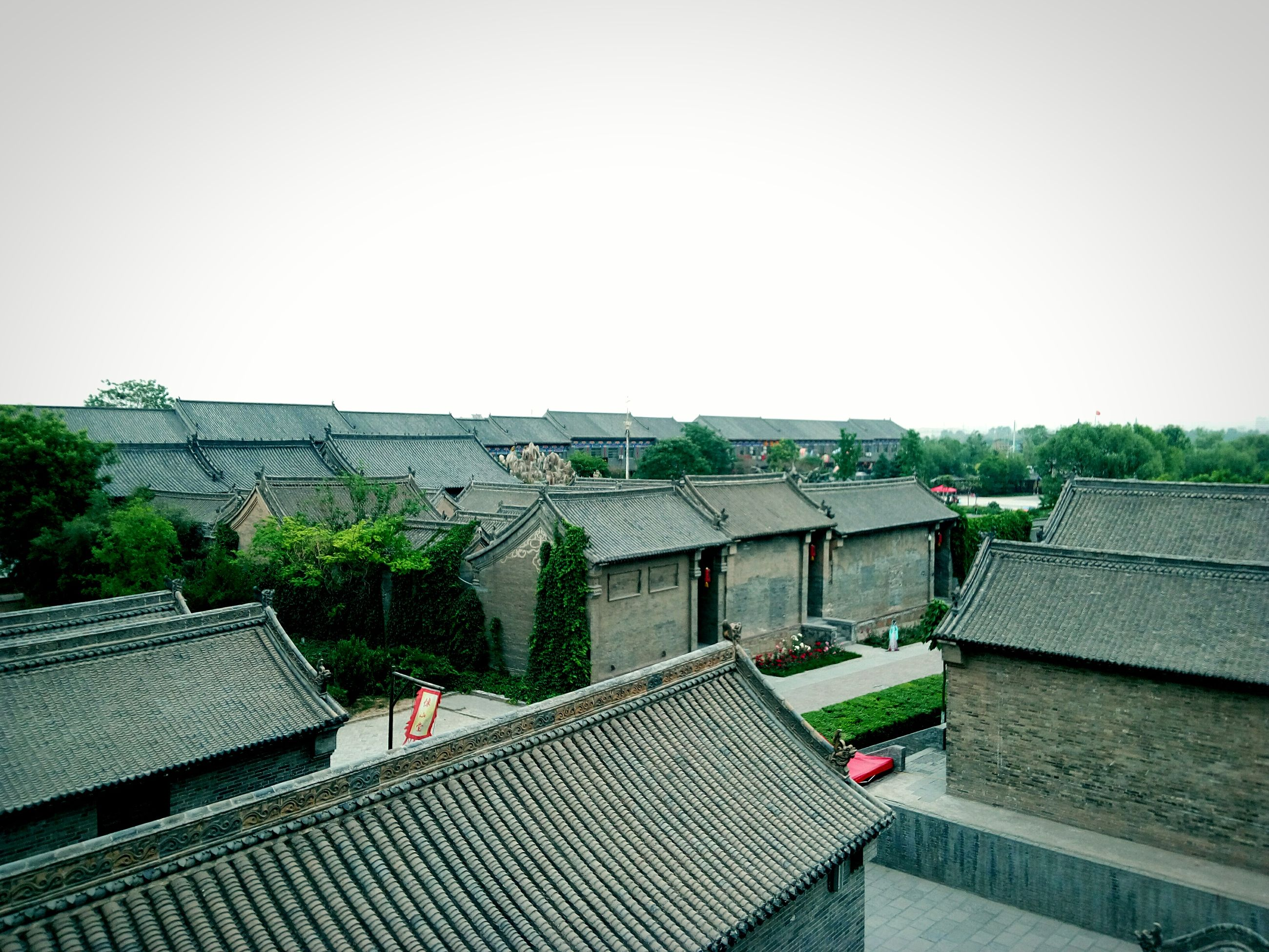 building exterior, architecture, built structure, clear sky, copy space, roof, house, high angle view, residential structure, residential building, day, outdoors, residential district, tree, city, sky, town, roof tile, no people, rooftop