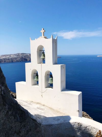 Beautiful views of Greek shrine on the cliffs of the caldera of Santorini Megalochori Caldera Santorini EyeEm Selects Sea Water Sky Religion Built Structure Belief Building Exterior Sunlight Place Of Worship Horizon Over Water Beach Spirituality Nature Day Outdoors No People Architecture Blue
