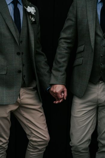 Midsection of gay couple holding hands