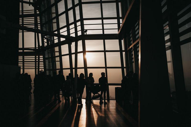Silhouette people walking in corridor of building
