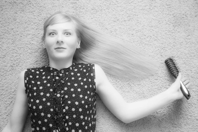 Portrait of young woman holding hairbrush against wall
