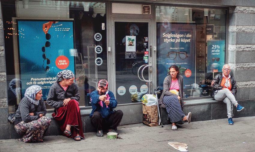 People sitting on street in store