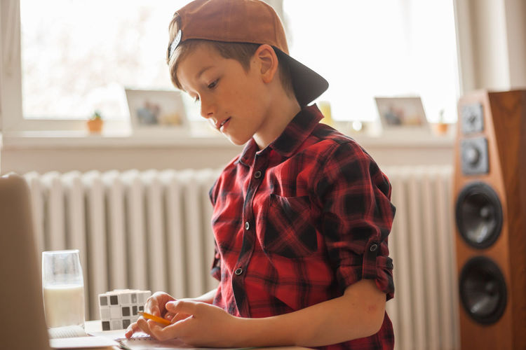 Cute boy with a cap studying at home due to coronavirus epidemic.