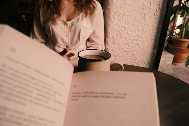 Book And Coffee In Front Of Woman Smoking At Home