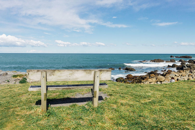 Empty Bench By Rocks Against Sea