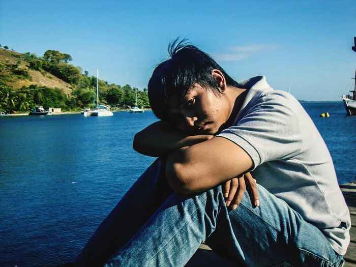 Portrait of young man sitting on pier over sea against sky