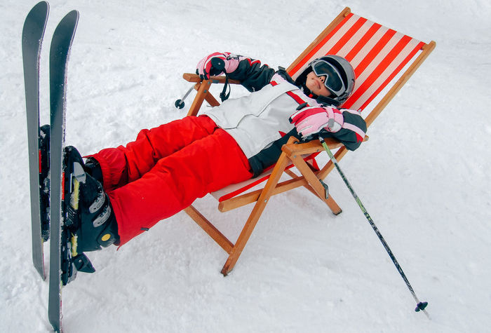 Skiing Wintersport Boys Child Childhood Cold Temperature Day Full Length Helmet High Angle View Lying Down One Person Outdoors People Real People Ski Ski Holiday Snow Snowboarding Sunchair Warm Clothing Winter Shades Of Winter