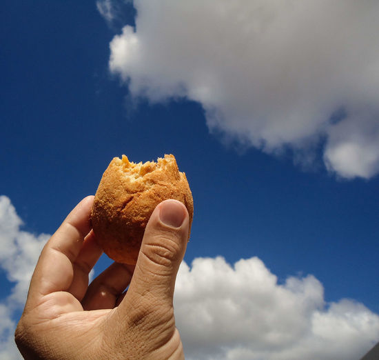 A hand holding a drumstick with sky in the background
