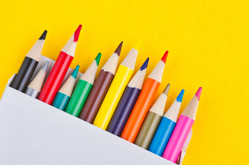colourful pencils in the white box over yellow background Multi Colored Still Life Variation Art And Craft Choice Indoors  Studio Shot Pencil Close-up No People Writing Instrument Large Group Of Objects High Angle View Creativity Colored Pencil Side By Side Arrangement Table Craft Yellow Art And Craft Equipment Variety