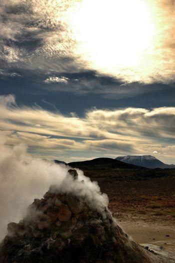 Smoke emitting volcanic landscape against sky