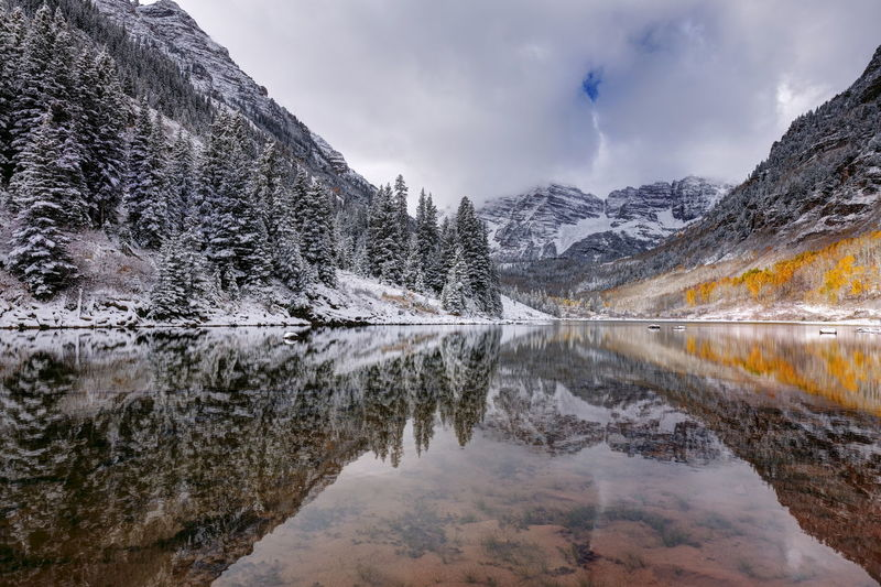 Scenic View Of Maroon Lake And Snowcapped Mountains Against Cloudy Sky