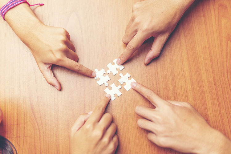 Adult Finger Group Of People Hand High Angle View Holding Human Body Part Human Hand Indoors  Jigsaw Piece Jigsaw Puzzle Leisure Activity Lifestyles Men People Puzzle  Real People Relaxation Togetherness Women