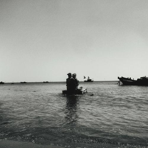 Double exposure of man walking in sea against clear sky