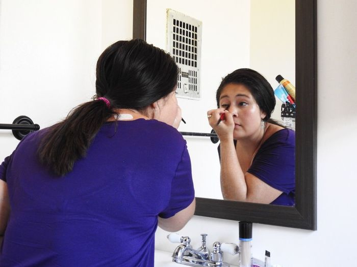Reflection Of Woman In Mirror While Applying Eyeliner At Home