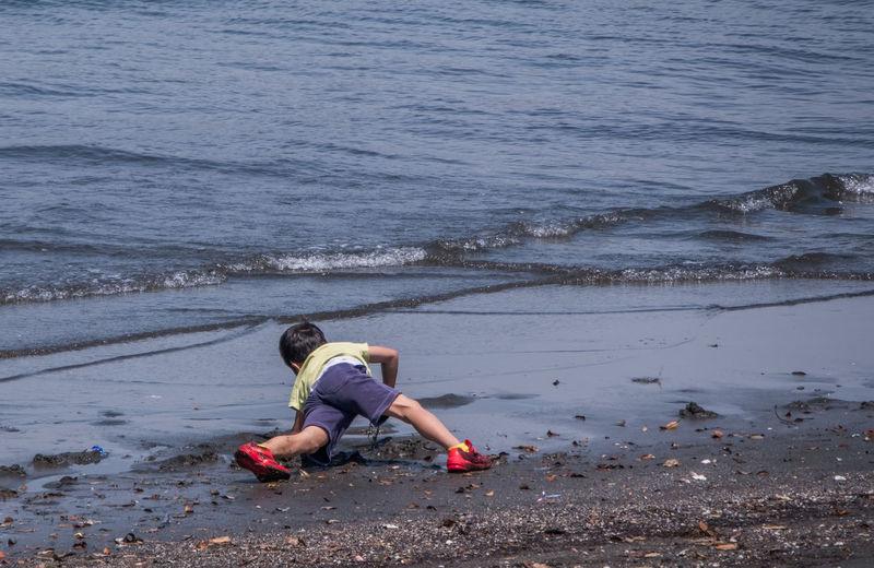 Full length of girl sitting on beach
