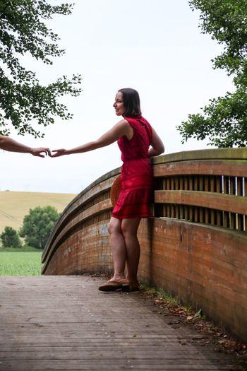 Cropped hand on man reaching girlfriend standing on footbridge at park