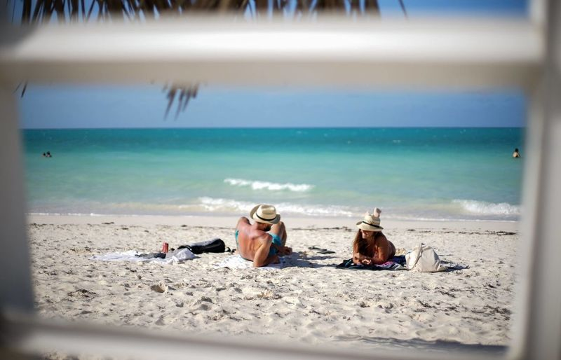 Man and woman relaxing at beach seen through railing