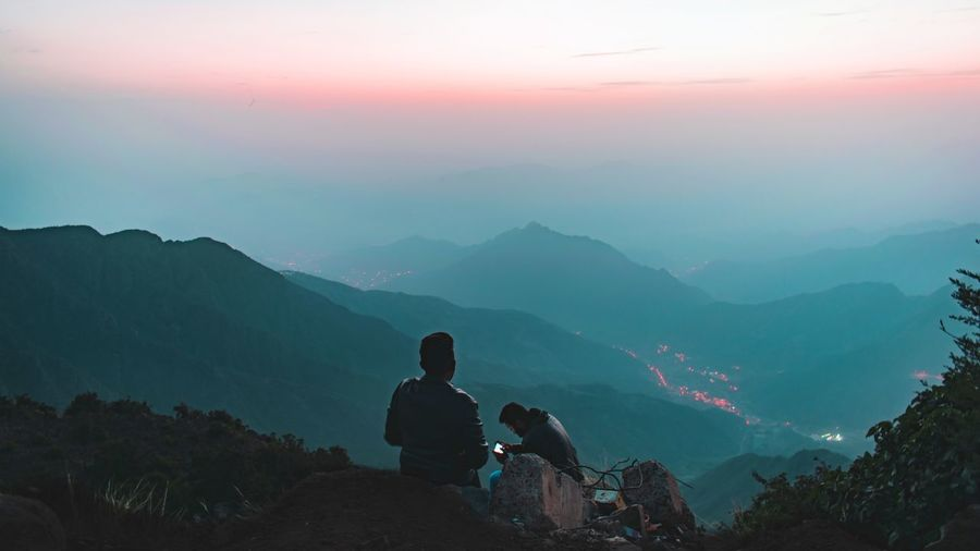People sitting on mountain against sky during sunset