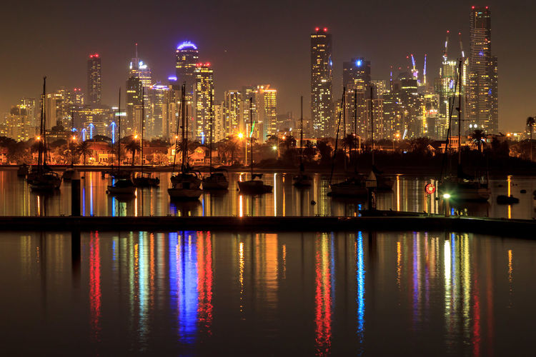 Illuminated buildings reflecting on river against sky at night