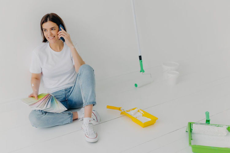Full length of woman holding color swatch talking on phone while sitting on floor at home