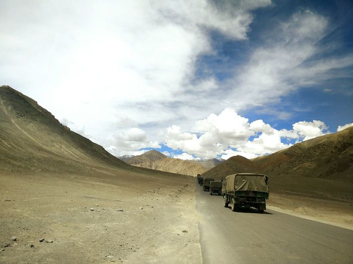 Military Trucks On Mountain Road Against Sky