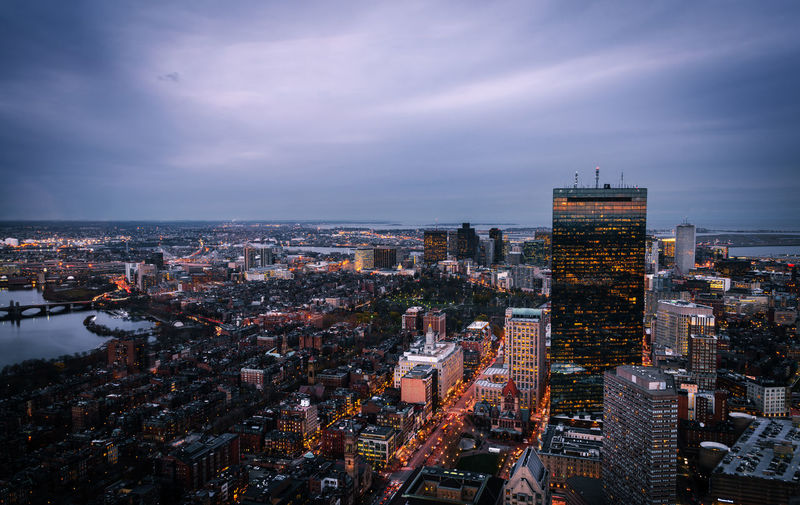 Aerial view of illuminated city buildings against cloudy sky at dusk