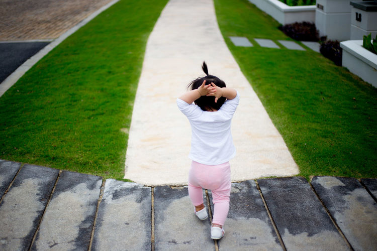 Rear View Of A Girl Walking Outdoors