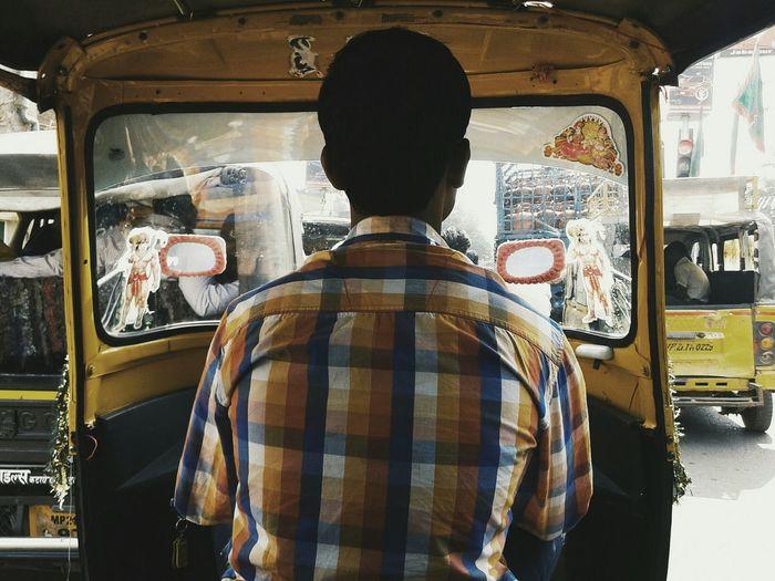 Rear view of man driving auto rickshaw