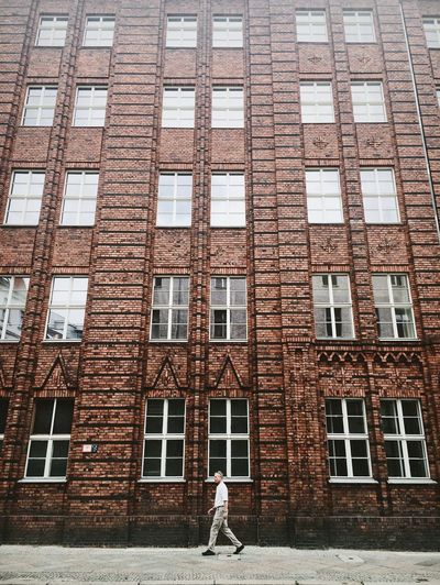 Architecture Berlin Brick Wall City Man Passerby Brick Building Building Exterior Built Structure Daily Life Day Old Buildings One Person People Red Wall Streetphotography Walking Windows The Week On EyeEm The Architect - 2018 EyeEm Awards