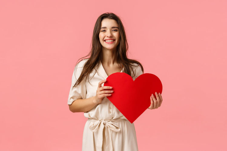 Woman holding heart shape against red background