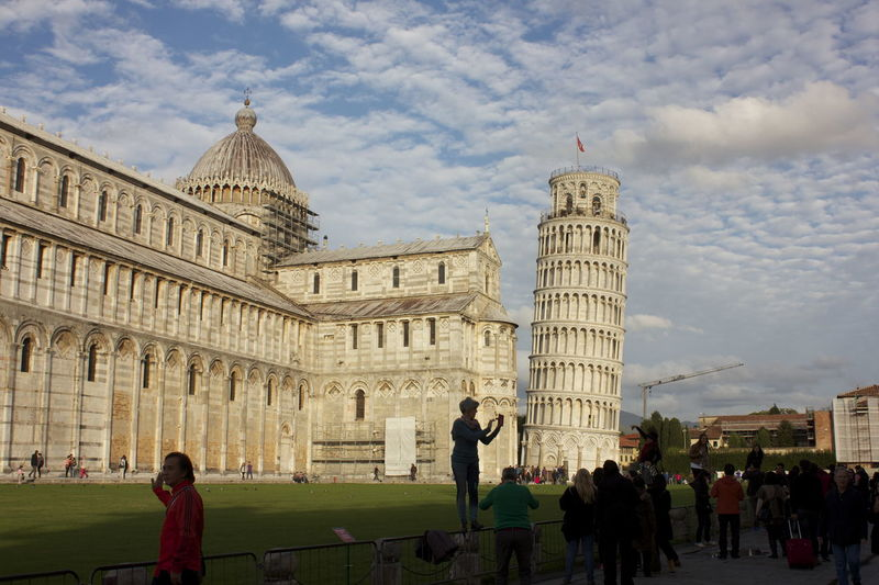 People by pisa cathedral against sky in city