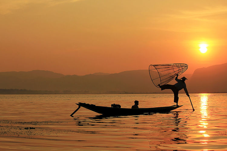 Silhouette fisherman holding cone shaped fishing net while standing on boat in lake during sunset