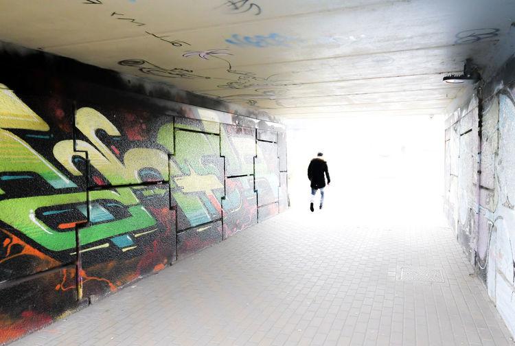 Rear view of man walking in graffiti on wall