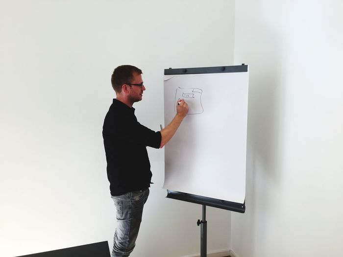 Man drawing in paper against wall