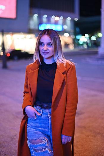 Portrait of beautiful woman in illuminated city at night