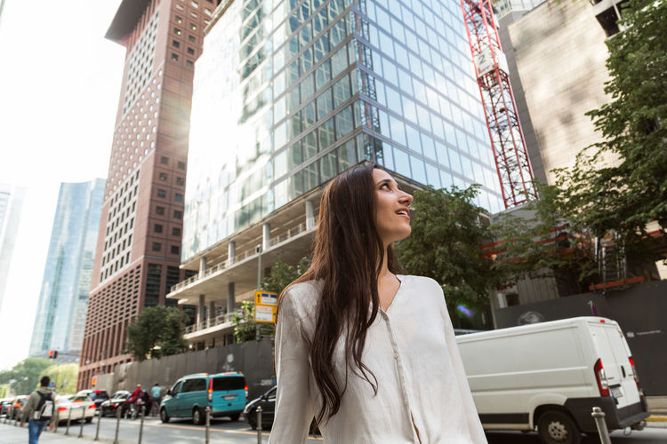 Low Angle View Of Woman Smiling While Standing Against Buildings In City