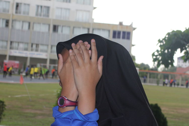 Close-up of woman covering face while standing in campus