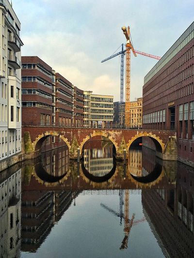 Arch bridge over river amidst buildings in city